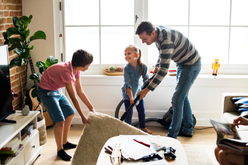 children helping a dad lifting carpet to clean hard wood floor in a living room