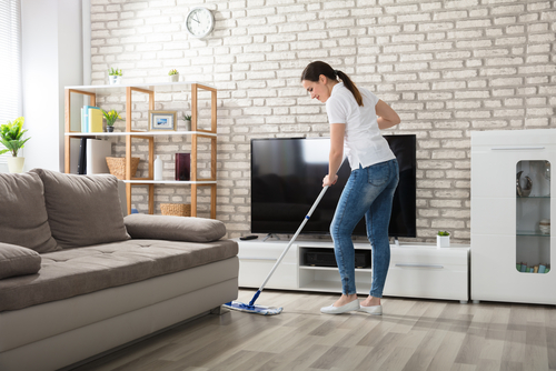 woman cleaning hard wood floor in a modern cozy living room